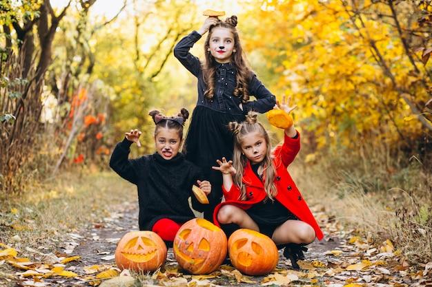Meninas crianças vestidas em trajes de halloween ao ar livre com abóboras