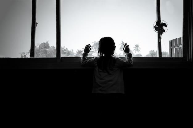 Meninas da criança asiática estão em pé no escuro, olhando pela janela, humor triste