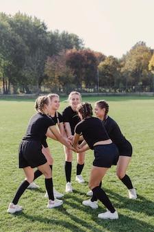 Meninas da equipe feminina, juntando as mãos