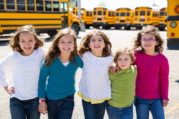 Meninas da escola amigos em uma fila andando de ônibus escolar