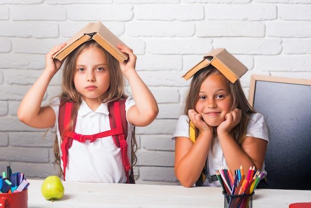 Meninas da escola. amizade de pequenas irmãs em sala de aula no dia do conhecimento.