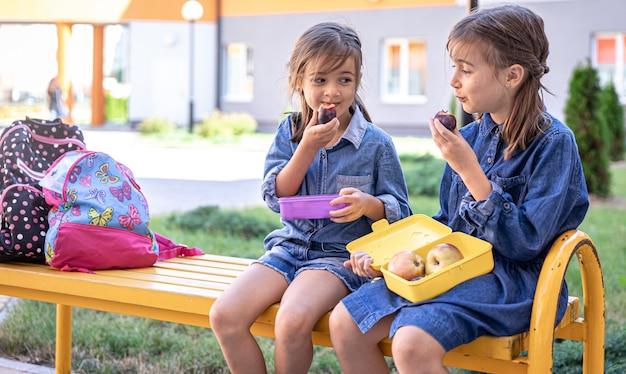 Meninas da escola, sentadas no banco do pátio da escola e comendo lancheiras.