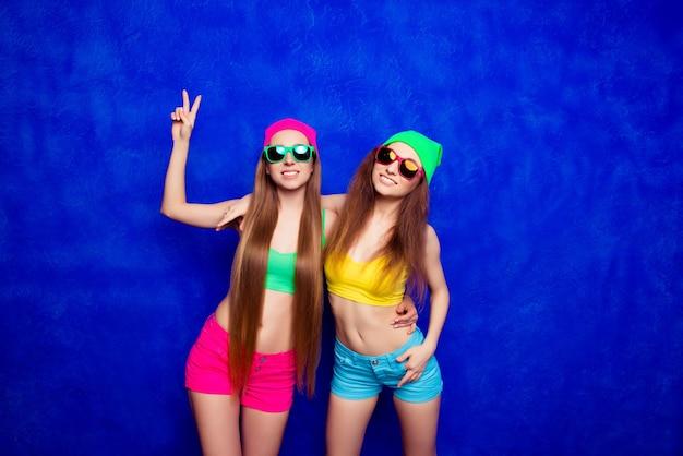 Meninas da moda hipster usam shorts coloridos, chapéu e óculos sorrindo
