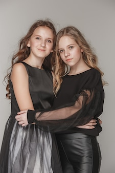 Meninas da moda juntos e olhando para a câmera sobre cinza