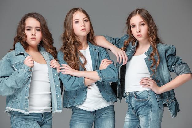 Meninas da moda juntos e olhando para a câmera sobre o estúdio cinza