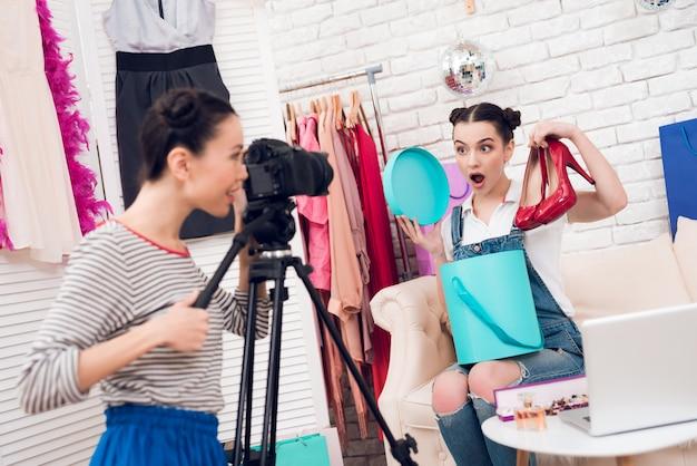 Meninas da moda seguram sapatos vermelhos com uma garota.