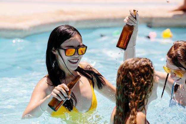Meninas dançando dentro de uma piscina com garrafas de cerveja