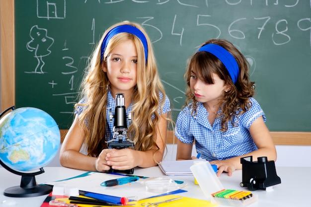 Meninas das crianças na sala de aula da escola com microscópio