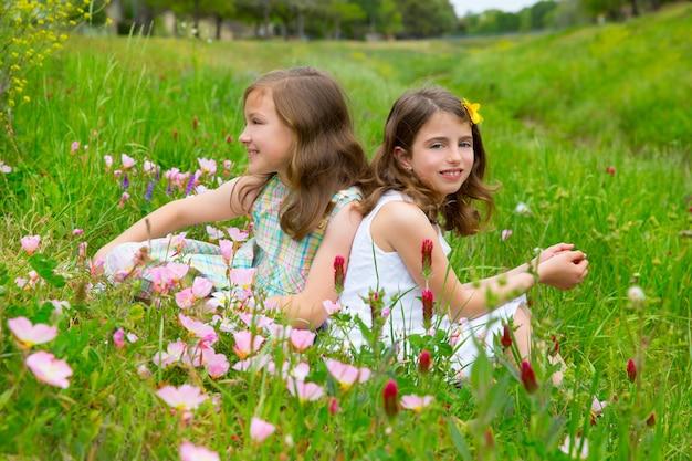 Meninas de amigos de crianças na primavera papoula flores prado