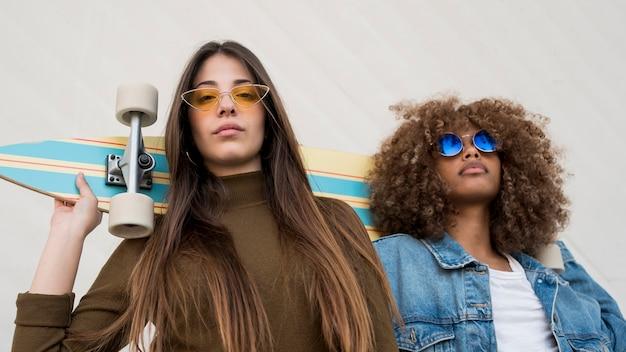 Meninas de baixo ângulo com óculos de sol