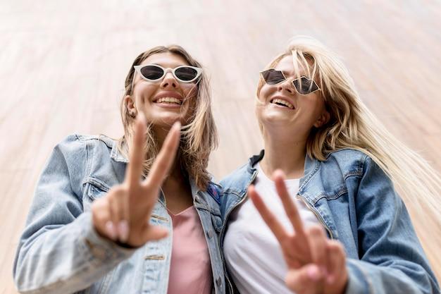 Meninas de baixo ângulo posando enquanto mostram o símbolo da paz