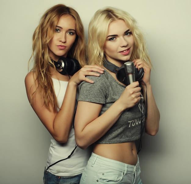 Meninas de beleza com um microfone, cantando e dançando
