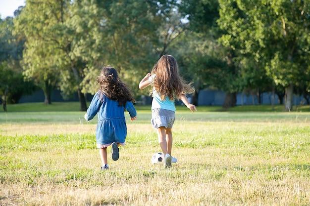 Meninas de cabelos negros ativas correndo para a bola de futebol na grama no parque da cidade. comprimento total, vista traseira. conceito de atividade infantil e ao ar livre