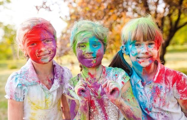 Meninas de criança europeus bonitos comemoram o festival de holi indiano com pó de tinta colorida no rosto e no corpo