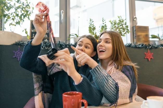 Meninas de estilo de vida de inverno no café se divertindo olhando velhos rolos de filme