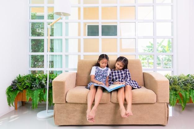 Meninas de estudante pouco gostam de ler o livro no sofá em casa