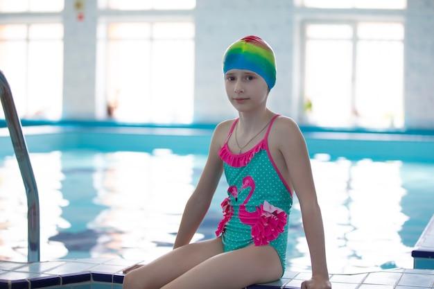 Meninas de maiô e touca de natação na piscina esportiva.