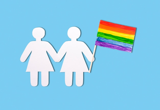 Meninas de papel em um fundo azul com uma bandeira de arco-íris lgbt