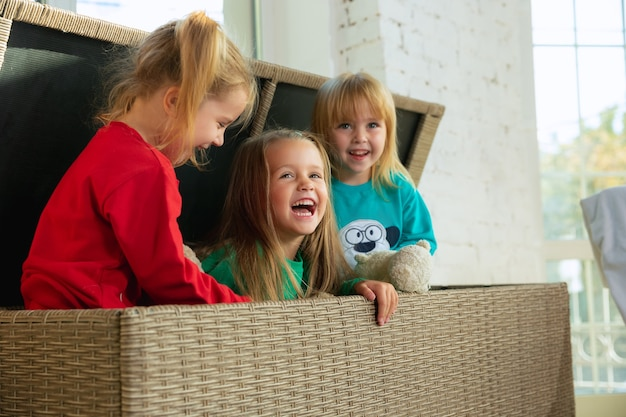 Meninas de pijama macio e quente brincando em casa. crianças brancas com roupas coloridas, se divertindo juntos. infância, conforto doméstico, felicidade. sentado em uma grande caixa de vime e rindo ..