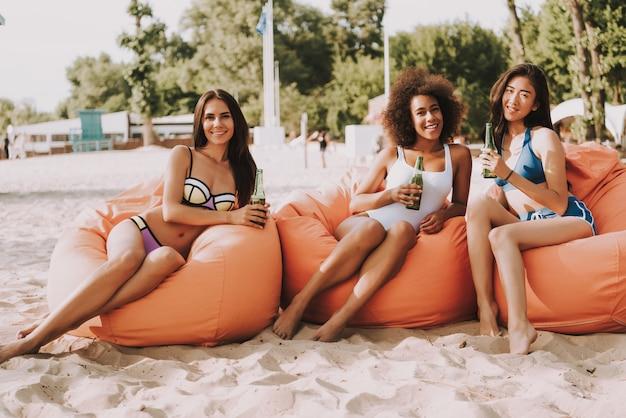 Meninas de raça mista linda de biquíni bebem cerveja.