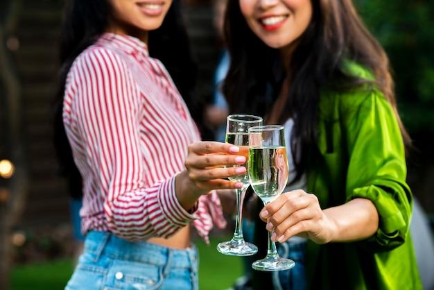 Meninas de smiley close-up com taças de champanhe