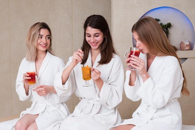 Meninas de tiro médio com bebidas saborosas