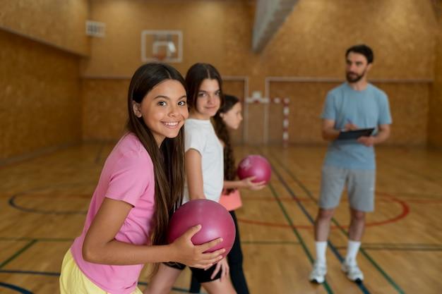 Meninas de tiro médio e professor de ginástica