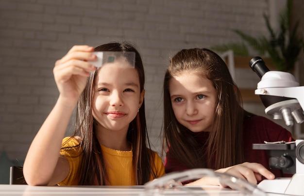 Meninas de tiro médio olhando para uma lâmina de vidro