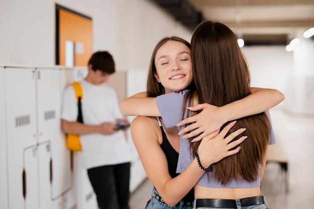 Meninas de tiro médio se abraçando