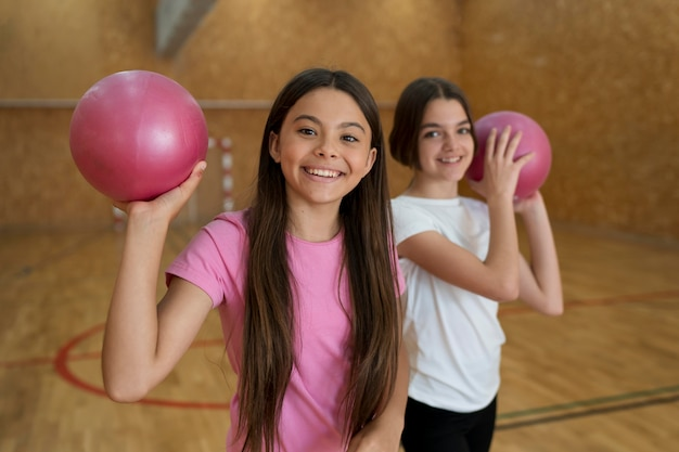 Meninas de tiro médio segurando bolas rosa