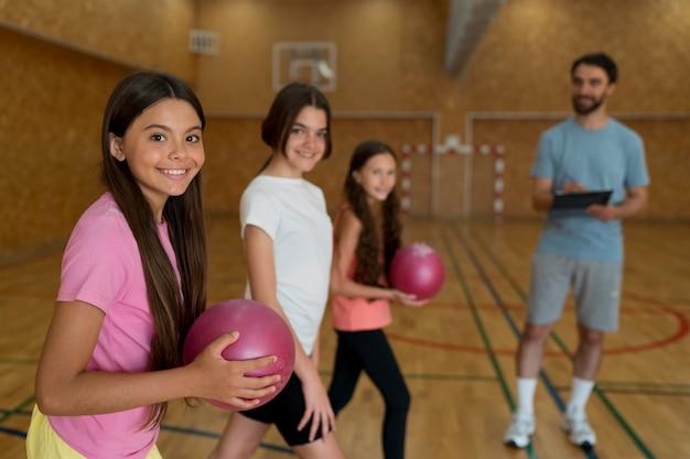 Meninas de tiro médio segurando bolas