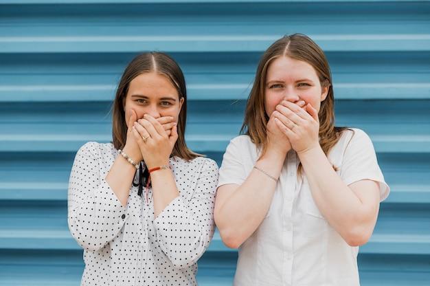 Meninas de vista frontal, cobrindo suas bocas