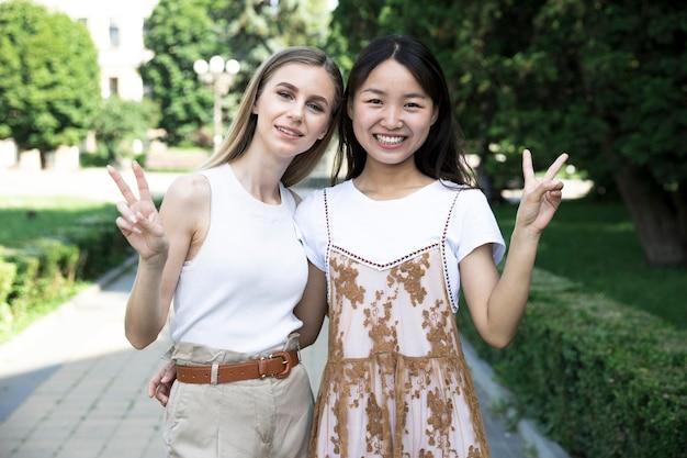 Meninas de vista frontal, fazendo o sinal da paz