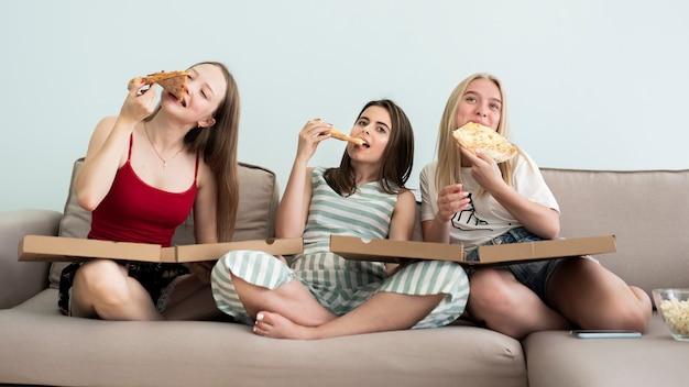 Meninas de vista frontal sentado no sofá e comendo uma pizza