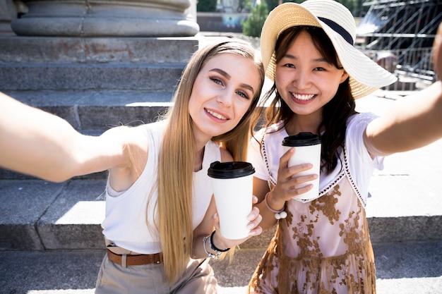 Meninas de vista frontal tomando uma selfie