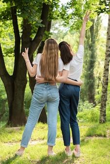Meninas de vista traseira fazendo o sinal da paz