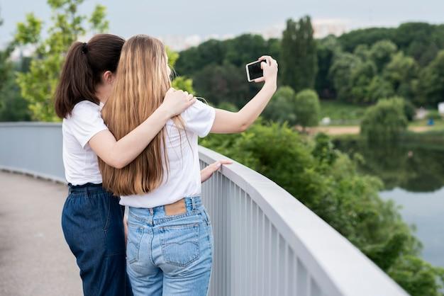 Meninas de vista traseira tomando uma selfie em uma ponte