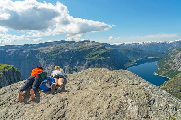 Meninas deitado na rocha acima do lago de montanha ringedalsvatnet, noruega.