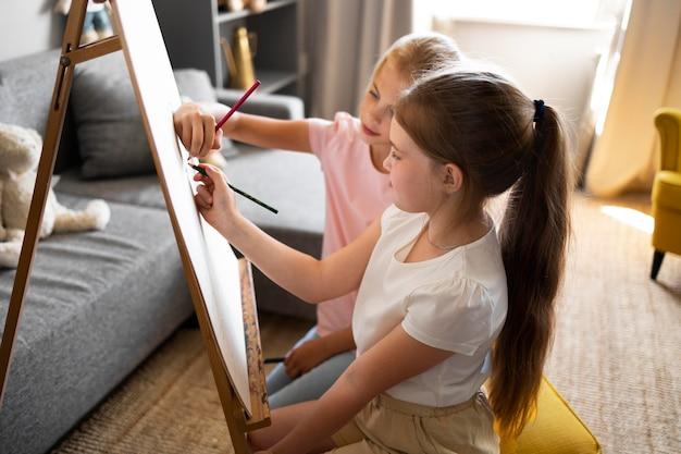 Meninas desenhando usando cavalete em casa juntas