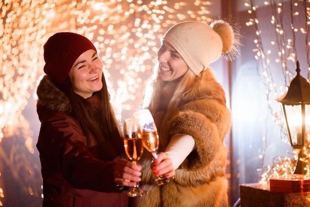 Meninas desfrutando de champanhe. retrato ao ar livre de senhoras na luz de fundo.