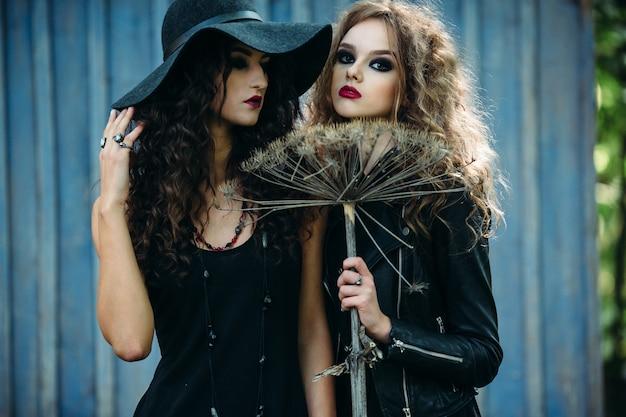 Meninas disfarçado como bruxas que levanta com uma vassoura