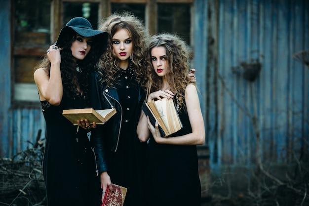 Meninas disfarçado como bruxas que prendem velhos livros nas mãos