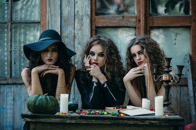 Meninas disfarçado como bruxas sentado a uma mesa com as mãos em seus rostos