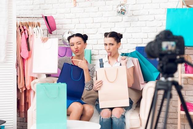 Meninas do blogger apontam para bolsas coloridas para a câmera