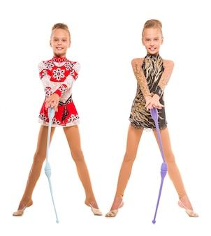 Meninas dos gêmeos que exercitam com macis ginástico.