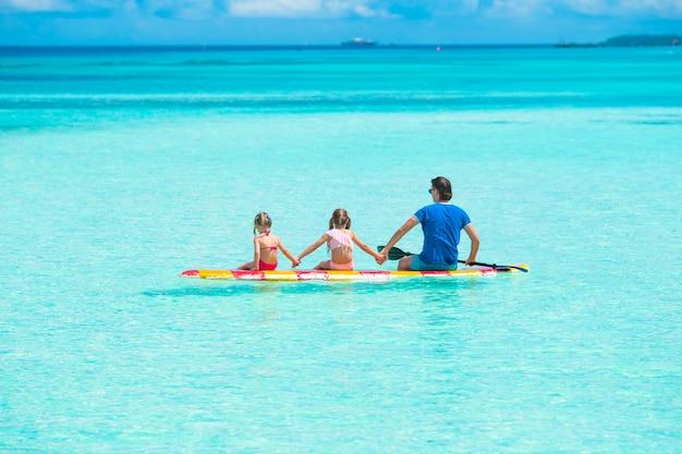 Meninas e jovem pai na prancha de surf durante as férias de verão