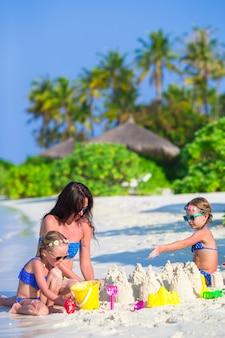 Meninas e mãe feliz brincando com brinquedos de praia nas férias de verão