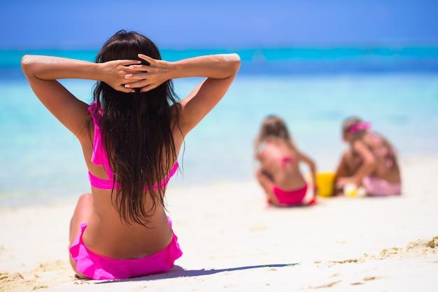 Meninas e mãe feliz durante as férias de praia