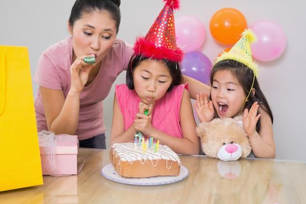Meninas e mãe soprando noisemakers em uma festa de aniversário