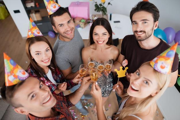 Meninas e meninos bebem champanhe e comemoram aniversário